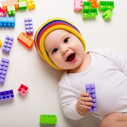 baby-boy-playing-with-multi-colored-constructor-white-wall_98296-1967